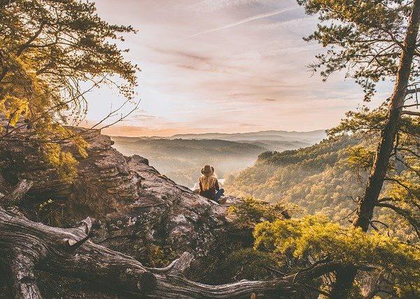 Frau sitzt auf einem Fels schaut auf den Wald hinab